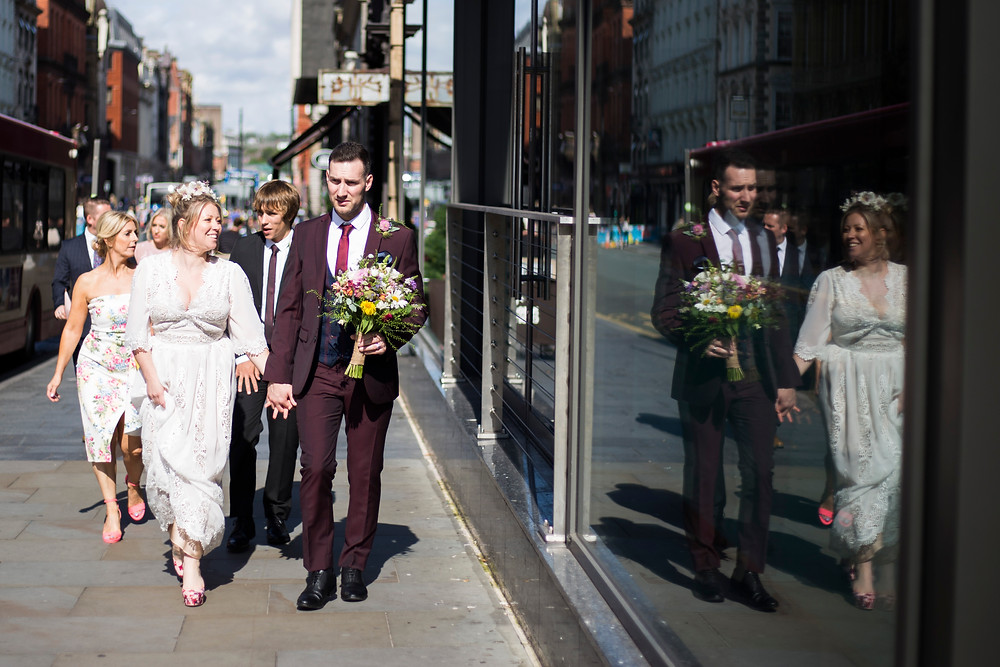 Bride, groom and wedding party walking through Liverpool to wedding reception