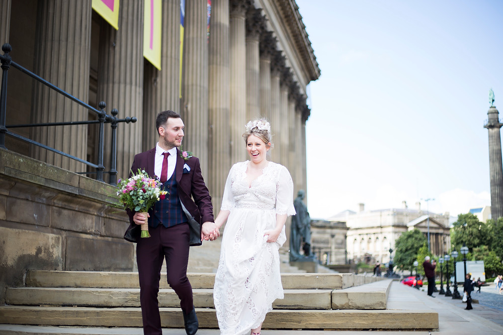 Bride and groom walking down the steps of St Georges Hall