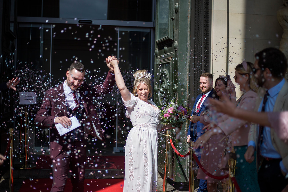 Bride and Groom covered in confetti outside St Georges Hall Liverpool
