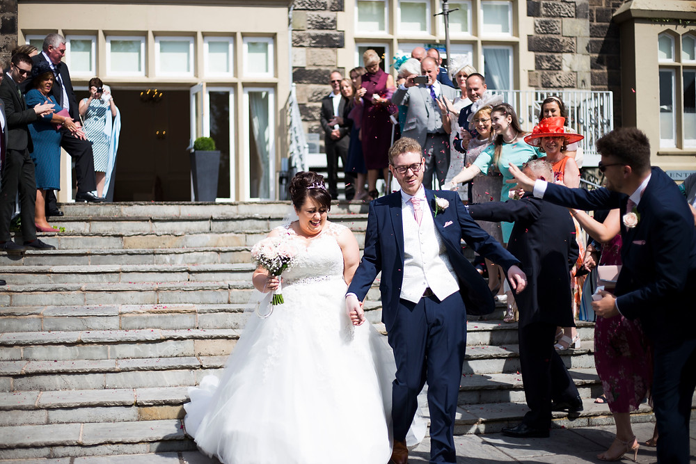 bride and groom covered in confetti on steps of West Tower wedding venue