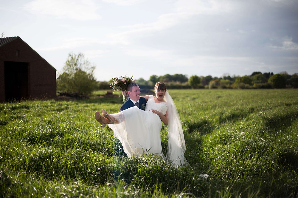 Groom carrying bride through field Parr Hall farm wedding