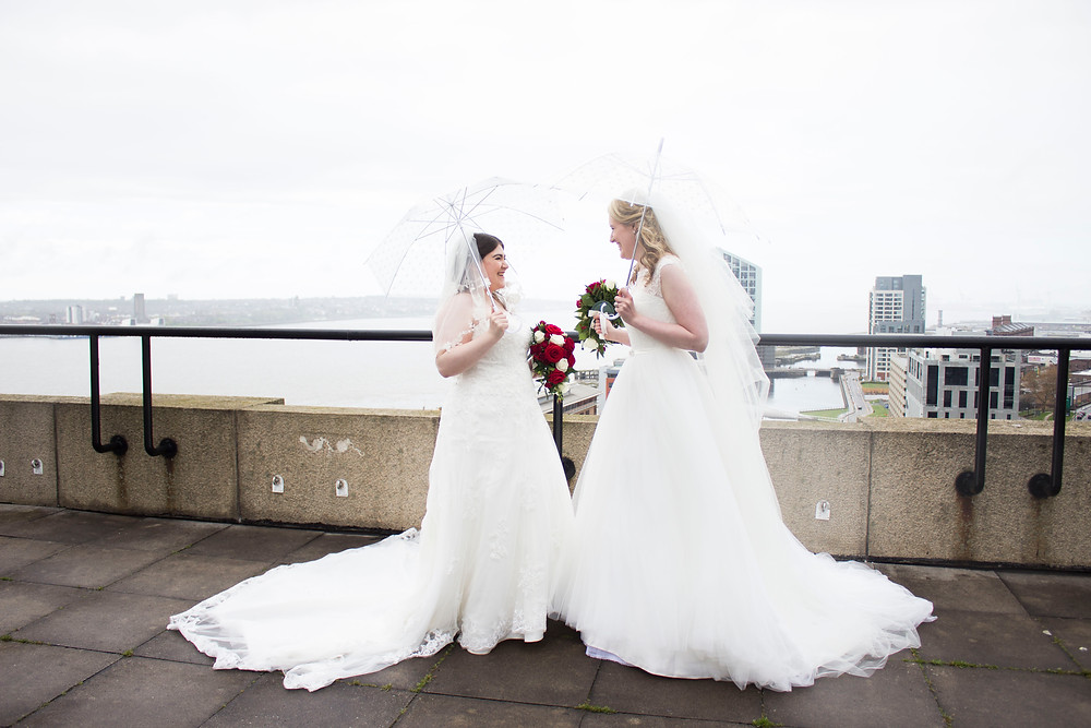 on the roof of liver building with two brides on their wedding day