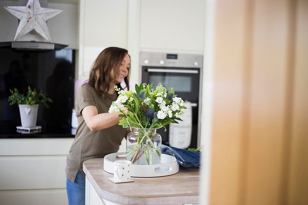 Claire arranging flowers in her kitchen as part of her personal branding shoot