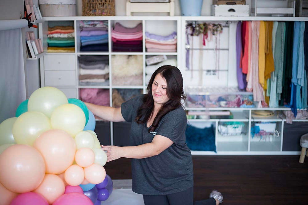 Newborn photographer Jemma arranging balloons in her studio. Relaxed behind the scenes and personal branding photography