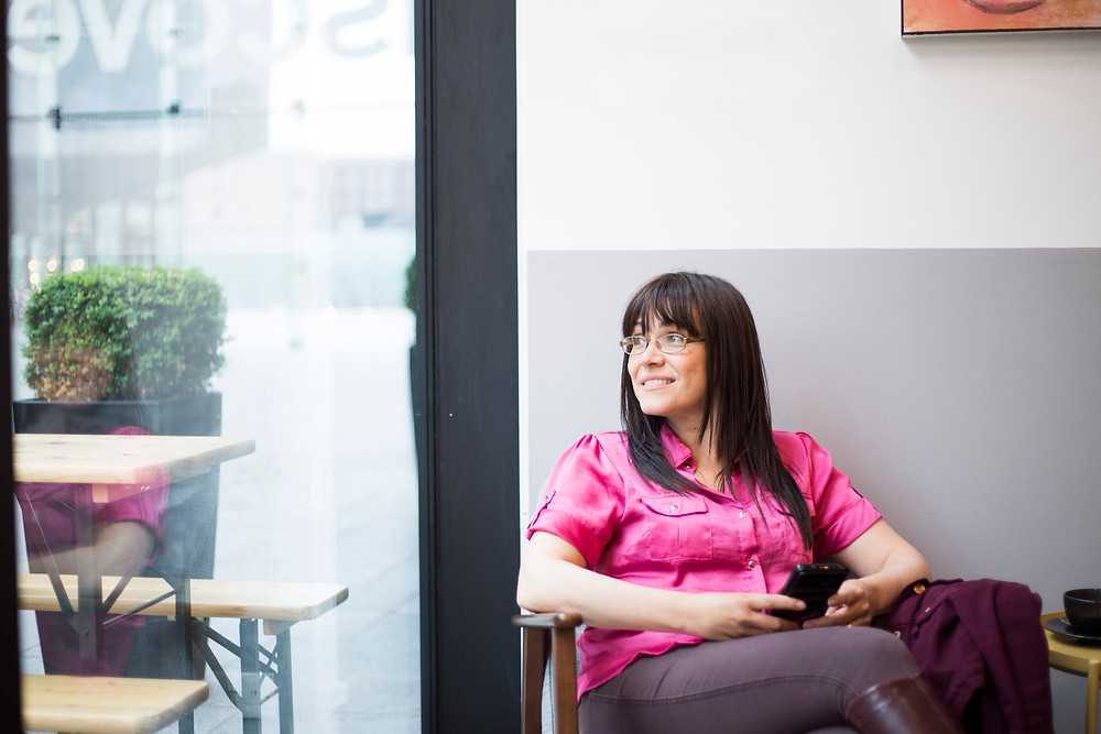 Chenoa Parr Pr sat in cafe looking out of window during personal branding photography shoot