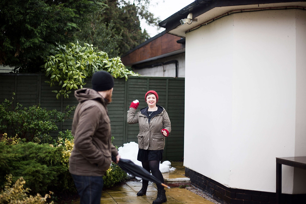 Bride to be throwing a snowball during pre wedding shoot at Thornton Hall Hotel