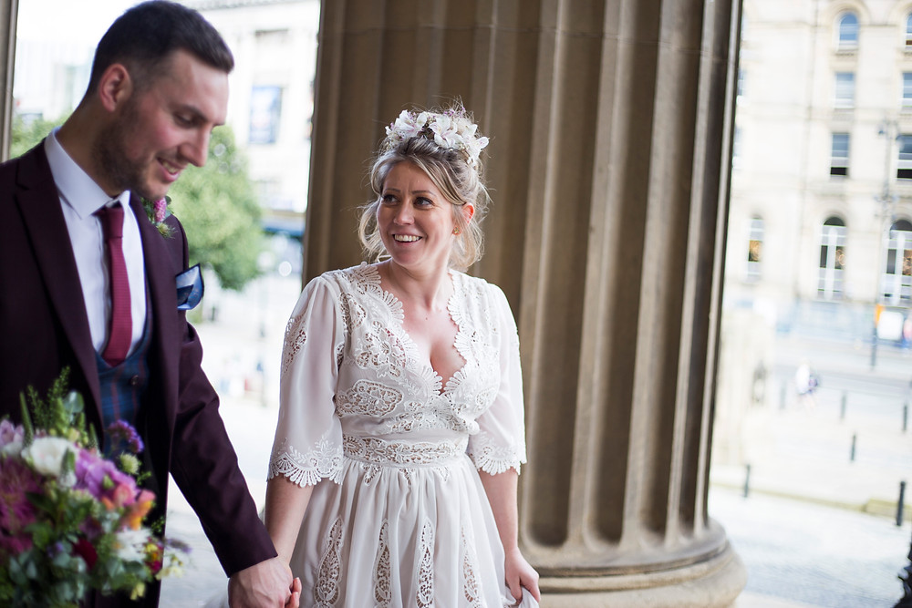 Bride and groom holding hands and laughing outside St Georges Hall