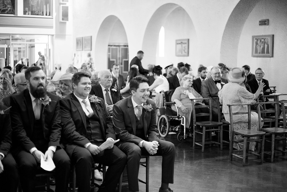 Groom and groomsmen waiting in church for bride to arrive