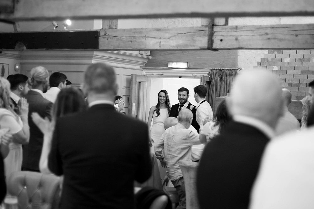 Bride and groom entering their wedding reception at The hayloft Allerton Manor