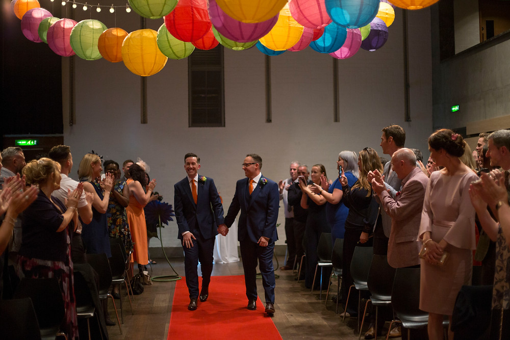 Grooms walking down the aisle at The Bluecoat performance space wedding