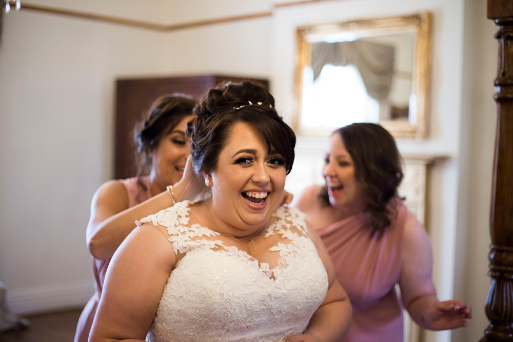 Bride laughing while bridesmaids put her veil in West Tower Liverpool Wedding