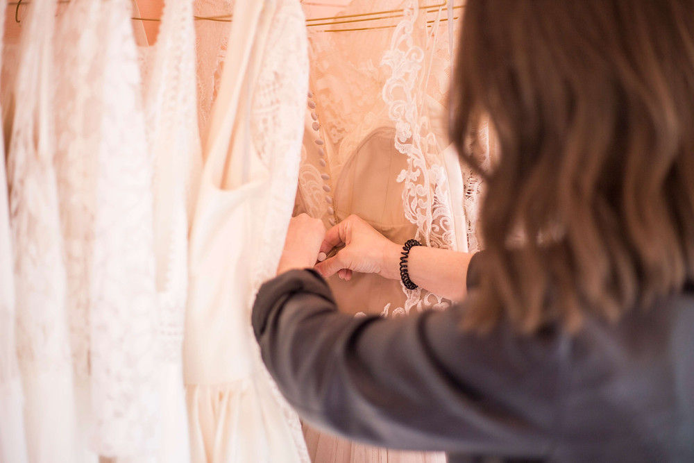 Flamingo Boulevard bridal studio Personal Branding Photography Bridal stylist looking through rack of wedding dresses