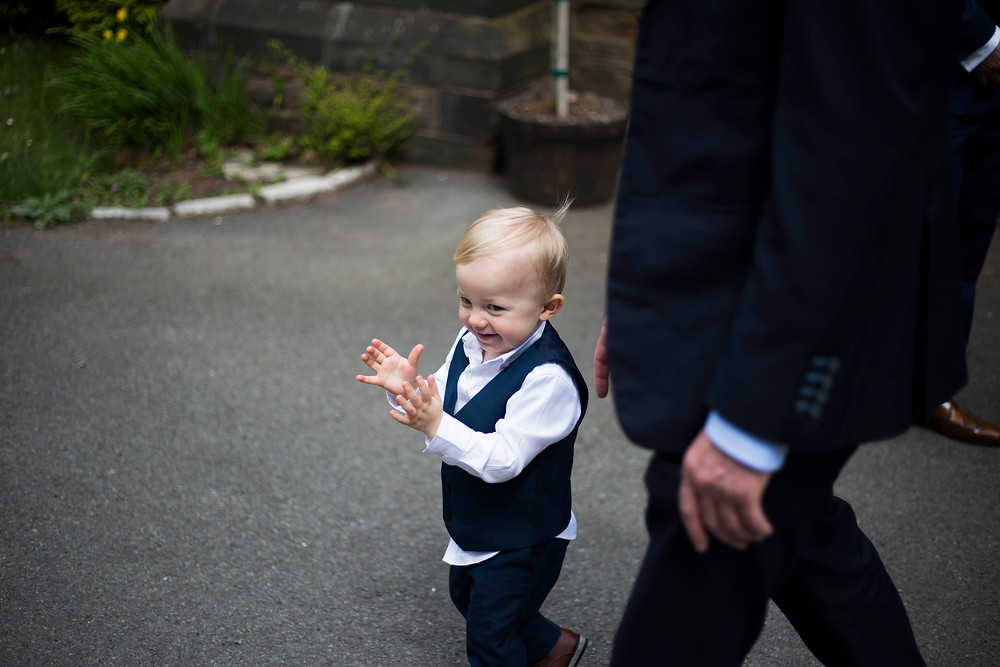 Bride and groom's son clapping as everyone leaves the wedding ceremony