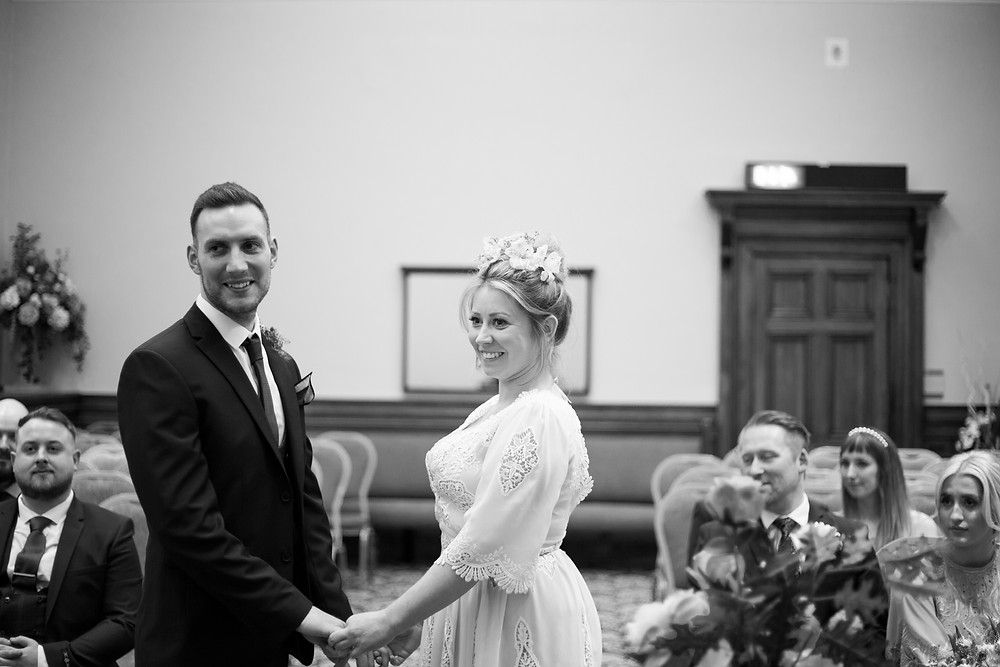 Bride and groom smiling and holding hands at St Georges Hall wedding