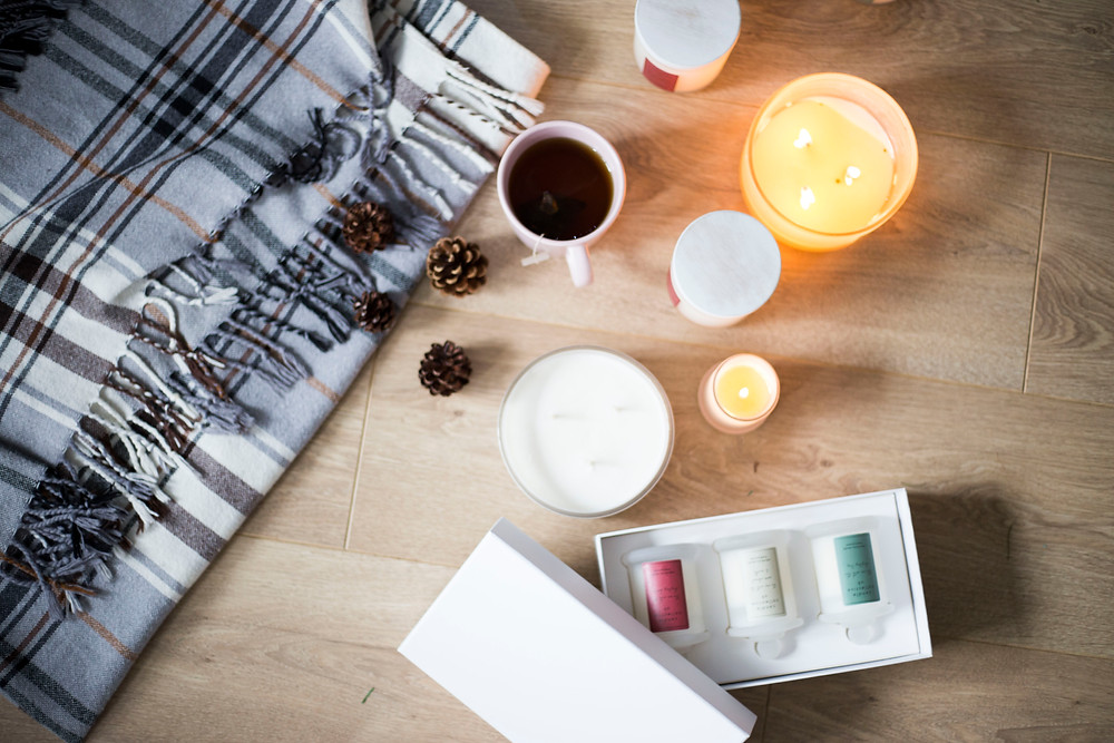 Candles, festive props and blankets laid on the floor with a Christmas theme. Product Photography Liverpool