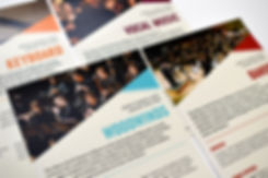 """Detail photo of four half-page handouts. The handout in the foreground reads """"Woodwinds"""" in blue text and shows a picture of a woodwind section performing."""