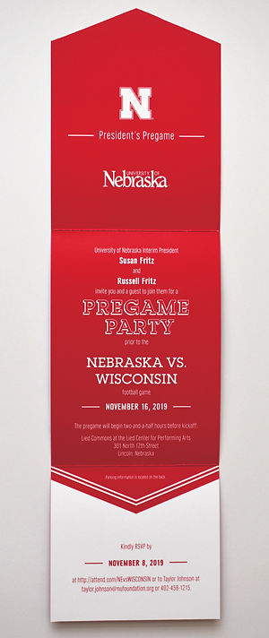 """Photo of an open tri-fold invitation. The top and center panels are red with white text, and the bottom panel is white with red text. The top panel shows the University of Nebraska logos and the words """"President's Pregame."""" The center panel contains information about a party hosted by the interim president of the University of Nebraska, prior to the Nebraska vs. Wisconsin football game on November 16, 2019. The bottom panel contains RSVP information."""