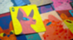 Close up photo of the ace of hearts playing card with other cards scattered underneath it. The illustration is of a sphynx cat on a yellow background.