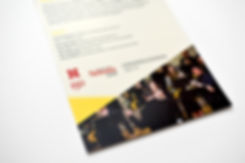 Detail photo of a half-page handout. Photo on the page shows a horn choir. Tan page with yellow accents.