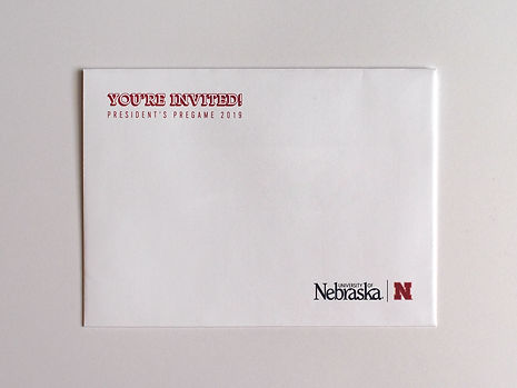 """Photo of a mailing envelope. Red text in the top left corner reads, """"You're invited! President's Pregame 2019."""" The bottom right corner contains a lockup of the University of Nebraska logotype and the University of Nebraska-Lincoln 'N.'"""