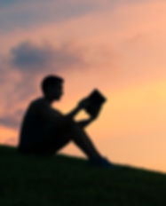 Young man reading a book in the park. .j