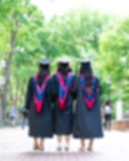 Image of three dark-haired women in grad