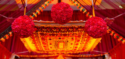 Brightly colored Indian ceremony site with red rose floral bundles hanging from ceiling