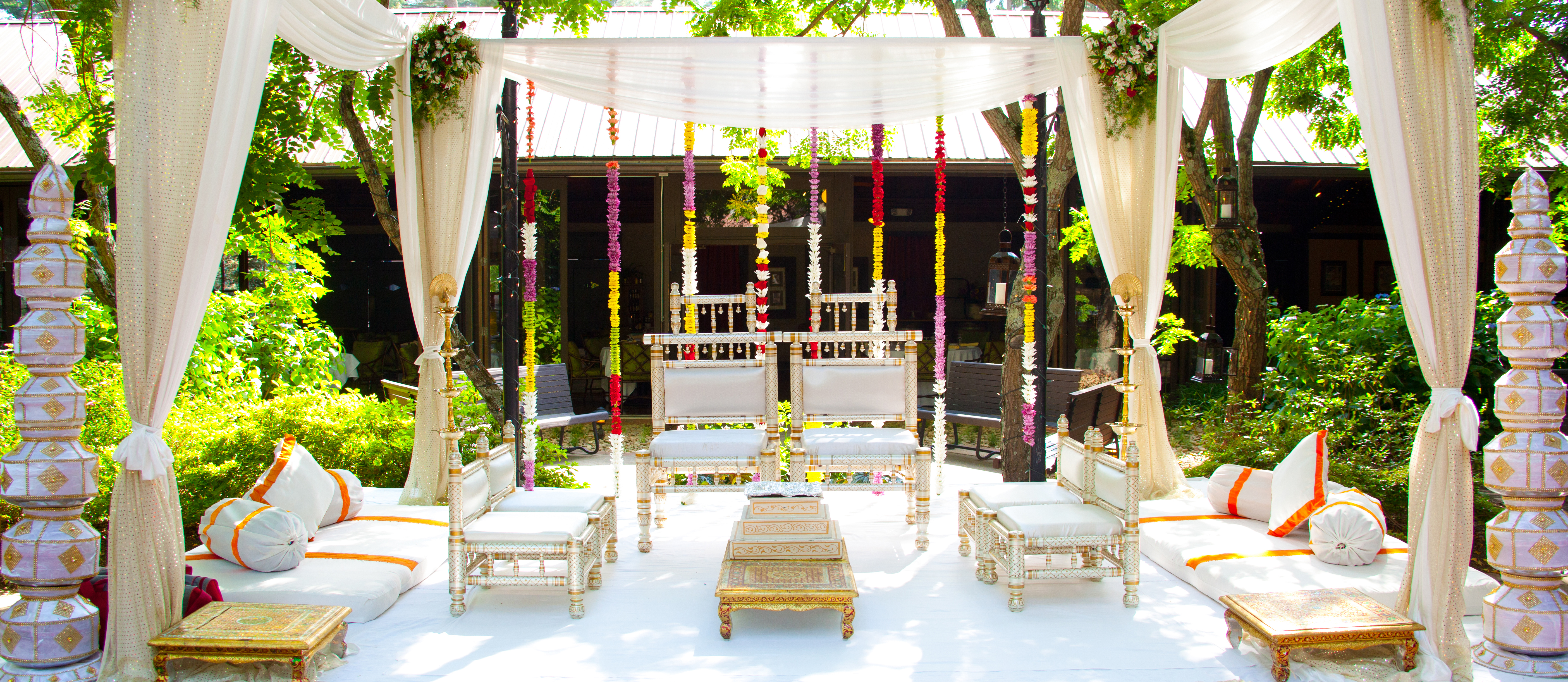 Beautiful outdoor ceremony set up with fabric canopy and floral decorations