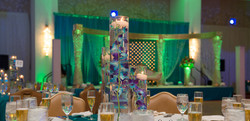 Indoor ceremony decor with blue green uplighting and large clear vases with floating orchids and can