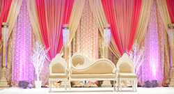 Beautiful stage decor with draped linens and ornate chairs