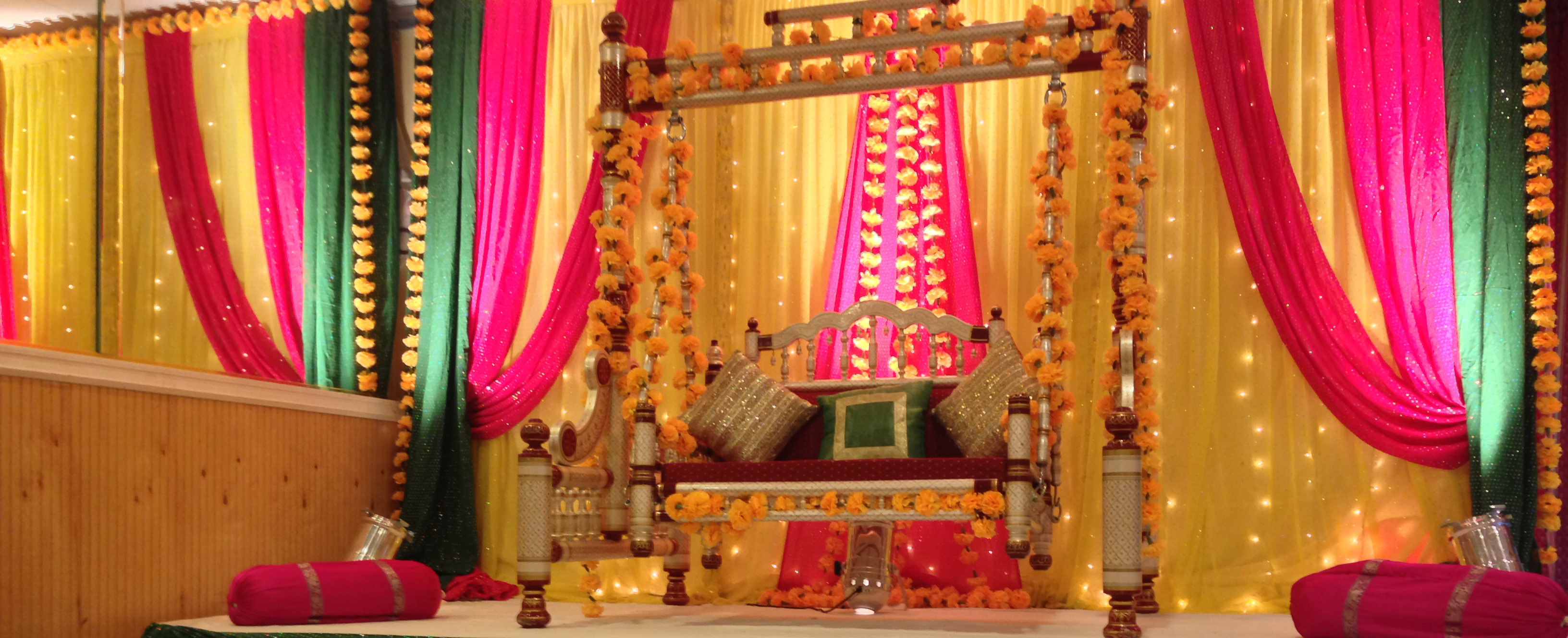 Indian wedding ceremony decor full of bright colored draped linens, florals, and ornate furniture