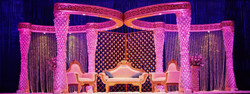 Grand stage setup for wedding ceremony with large geometric pillars creating a large open canopy