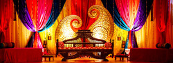 Brightly colored and ornate stage set up for Indian wedding ceremony.