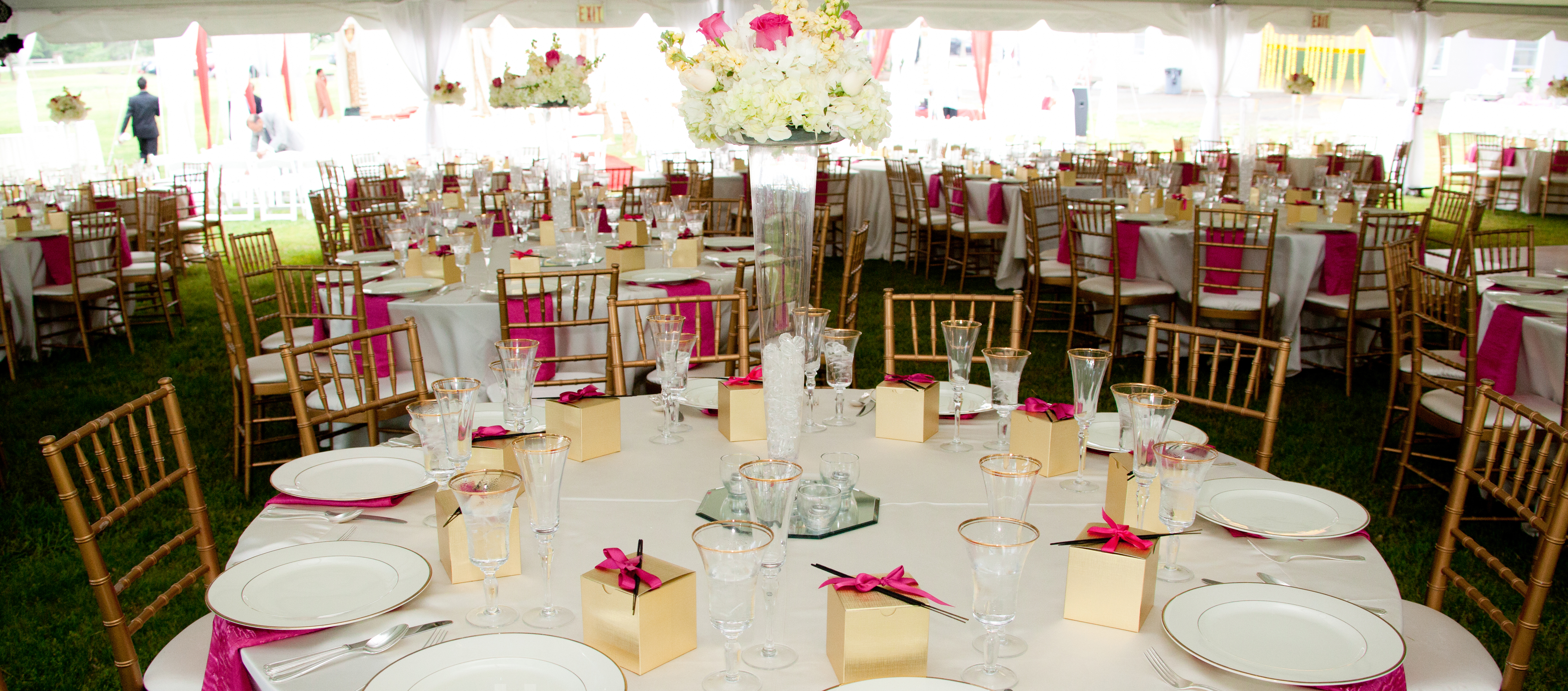 Outdoor reception with tables under white tents, gold chiavari chairs, white linens, and table decor