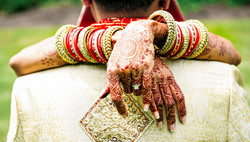 Bride in traditional Indian dress hugging groom - highlights henna decorated hands, beautiful bangle