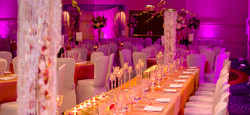 Ballroom with rectangular table dressed with candles and gorgeous plate settings
