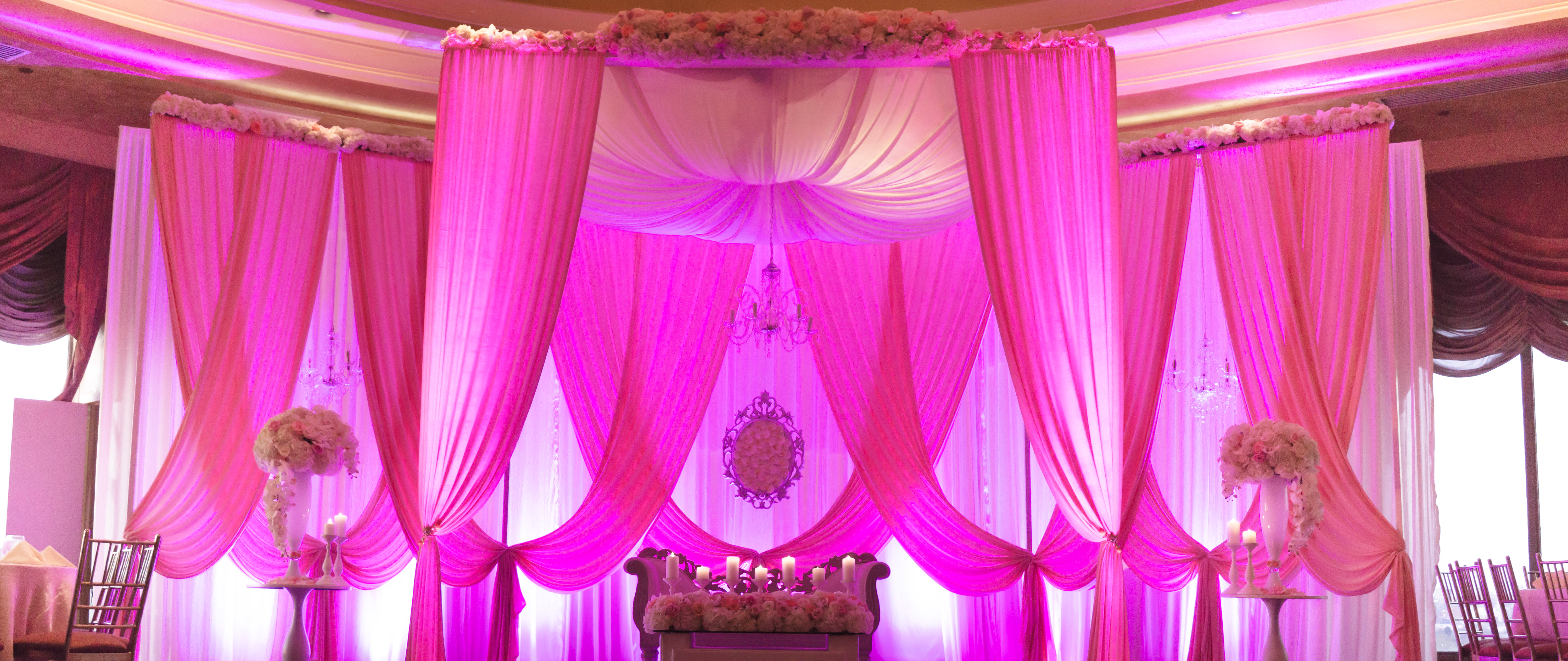 Floor to ceiling fuchsia colored draped linens creating a spectacular wedding ceremony site