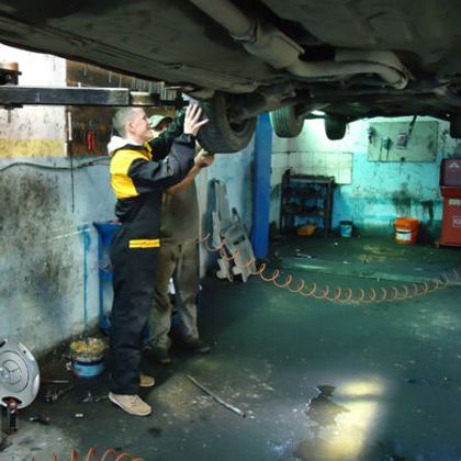 Albanian man repairing car in garage