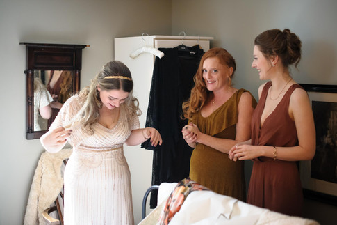 bride looking at her wedding dress with her bridesmaids - Galway wedding photograper