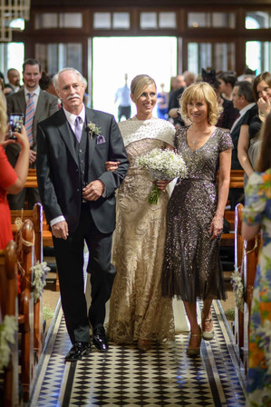 modern bride walking down the aisle with both parents - Galway wedding photograper