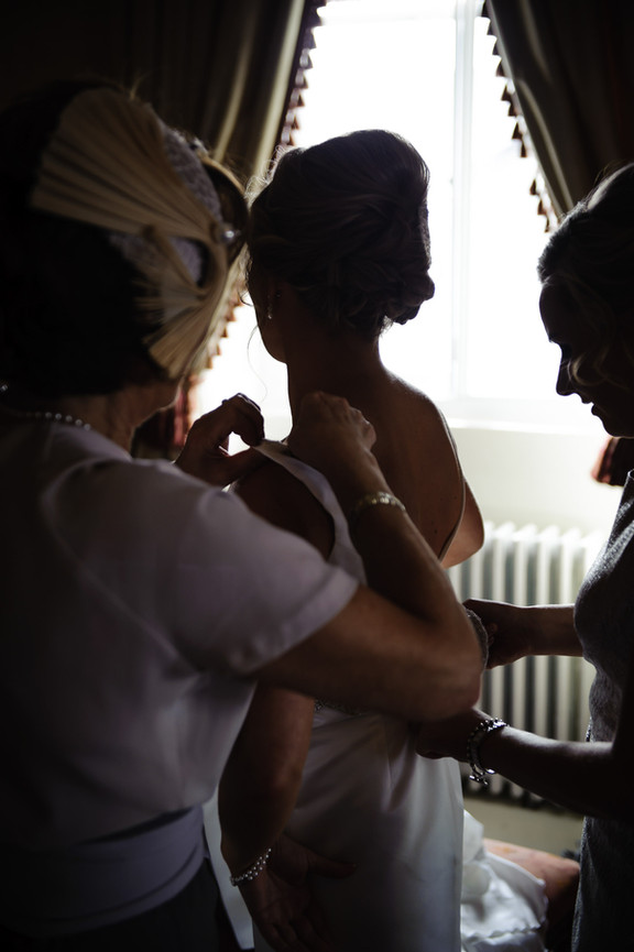 Finishing touches to the brides wedding dress - Galway wedding photograper