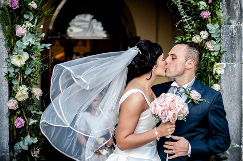 kissing at the church doorway - Galway wedding photographer