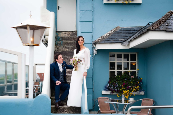 trendy bride and groom outside a teal building - Galway wedding photographer