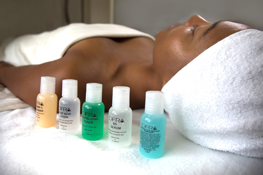 Image of woman lying on her back, wrapped in towels, preparing for a massage. A row of bottles of massage oil lie on the table next to her.