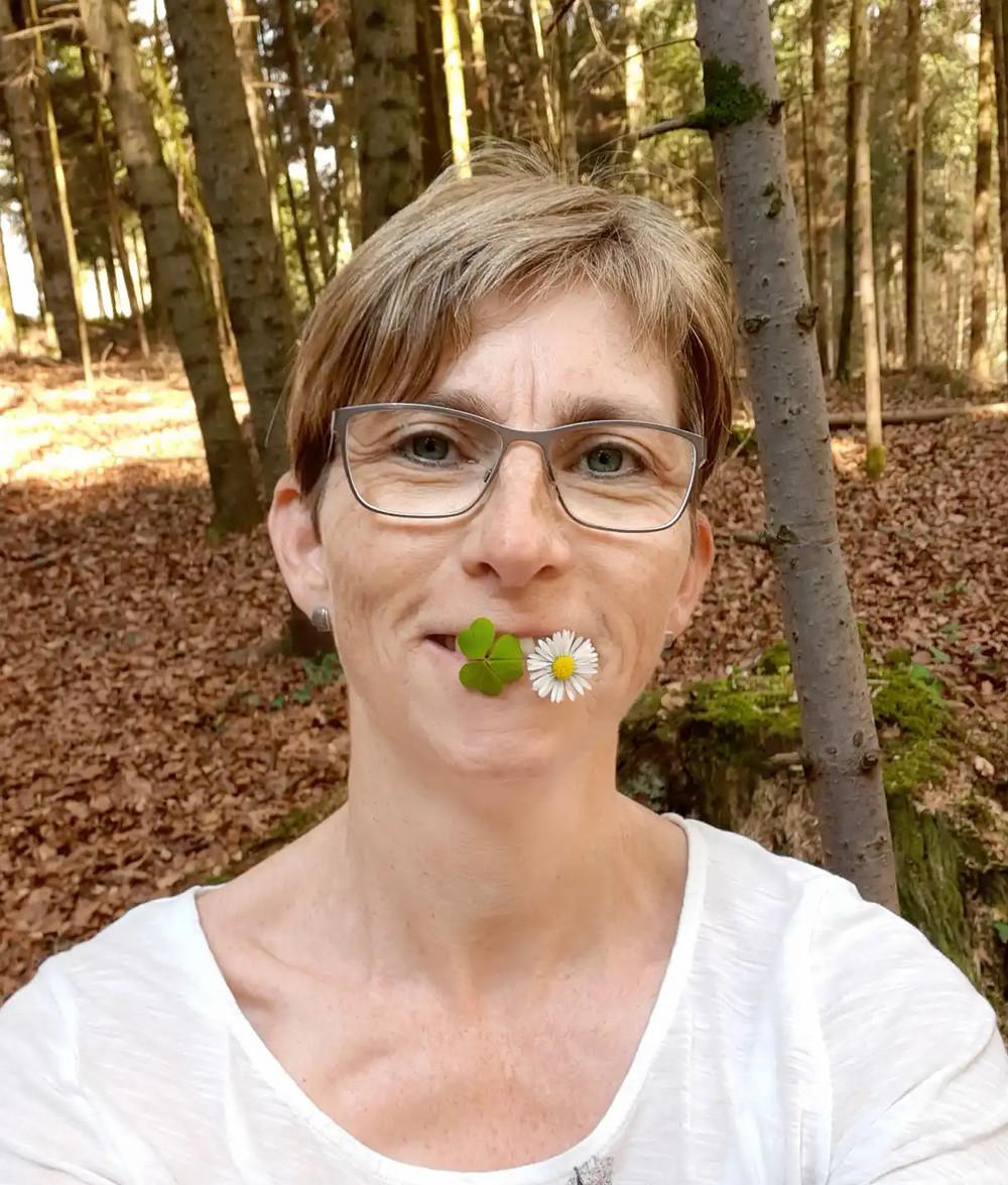 Alice hat ein Blatt Sauerklee und ein Gänseblümchen zwischen den Lippen. Sie im Wald inmitten von Bäumen..