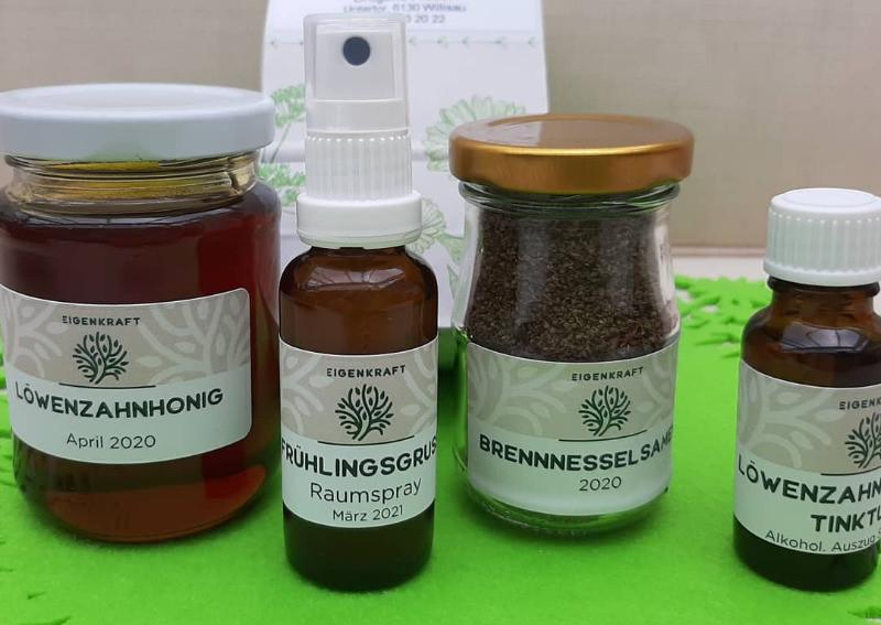 Wildkräuter Produkte: Zwei kleine Gläser beschriftet mit Löwenzahnhonig, Brennnesselsamen und zwei Fläschchen beschrifet mit Frühlingsgruss Raumspray und Löwenzahntinktur
