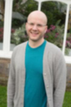 Tim Rosko headshot, smiling outside near some flowers