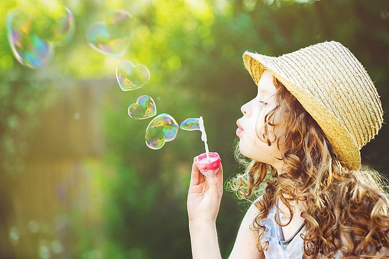 Cute girl blowing soap bubbles in a hear