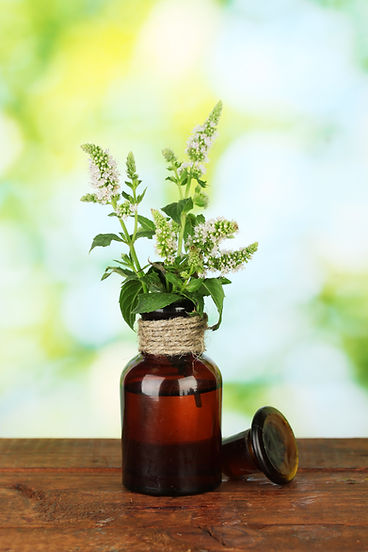 Essential oil and mint on green backgrou
