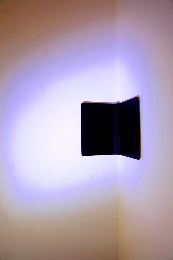 Simona Brinkmann, detail of exhibition view, Blank Stare Flat Hollow, solo show at Five Years, London. Upstage/Backstage spot strobe light, black leather covered notebook, corner. Light sculpture, installation, contemporary art.